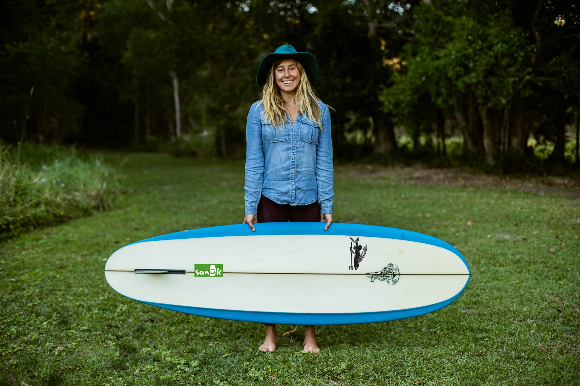 Lauren Hill stands in a plain of grass, with trees behind her, holding her surfboard and smiling.